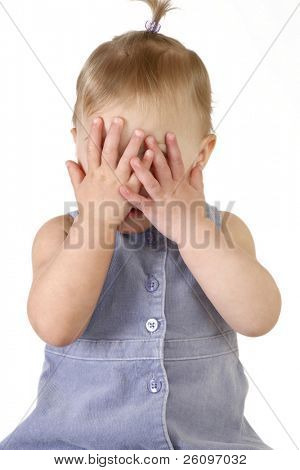 Baby girl playing peek-a-boo over white background.