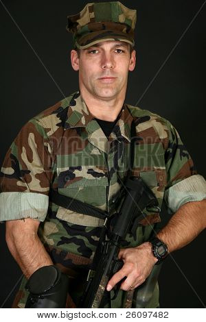 Attractive thirty something man in camo fatigues with paintball rifle.