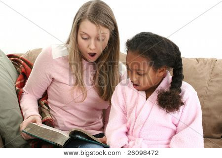 Adorable five year old African American Girl with babysitter reading.