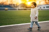 Cute Beautiful Girl Toddler Walking On The Street On Green Grass And Sunset Background. Happy Child  poster