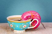 Pink Glazed Doughnut With Colorful Sprinkles Soaking Up Coffee From A Pink Floral Cup - Conceptualiz poster