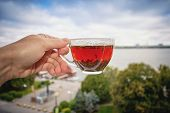 A Glass Cup With Tea In Hand Against A Background Of Urban Morning Scenery. Motivating Picture For A poster