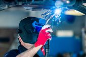 Male welds the automotive part in car factory with sparks poster