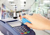 stock photo of debit card  - Human hand holding plastic card in payment machine in shop - JPG