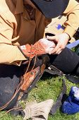image of bucking bronco  - rodeo cowboy preparing his glove and equipement for bull riding competition - JPG