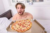 Man Bearded Handsome Guy Eating Cheesy Food For Breakfast In Bed. Guy Holds Pizza Box Sit Bed In Bed poster