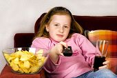 stock photo of potato chips  - little girl is zapping TV with cola and potatoe chips - JPG