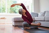 Senior woman exercising while sitting in lotus position. Active mature woman doing stretching exerci poster
