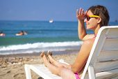 Cute Beautiful Young Woman Sunbathing On Sunbed On Sea Beach. Tanned Girl On Sea. Relax On Sea Beach poster