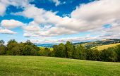 Beautiful Countryside In Early Autumn. Grassy Rolling Hills With Some Trees. Wonderful Cloudscape On poster