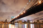 New York City Manhattan Bridge with city skyline at night illuminated over Hudson River.