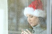 Sad Woman In Christmas Looking Down Through A Windos In A Rainy Day poster