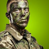 foto of special forces  - portrait of young soldier with jungle camouflage paint on a green background - JPG