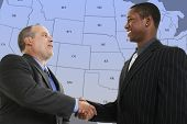 Two businessmen smiling and shaking hands in front of blue and grey US State Map.