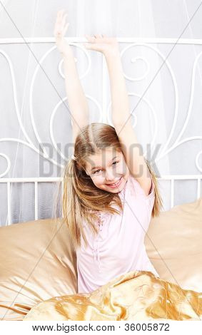 ten years' girl has woken up and stretches in bed