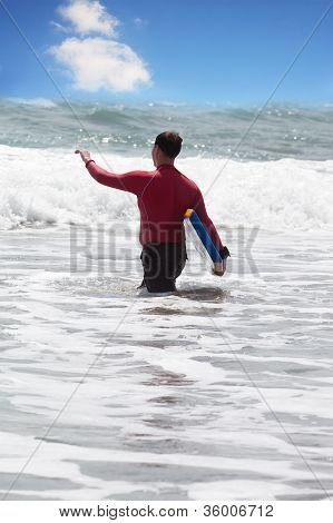 man with surf enters into water a back to the viewer