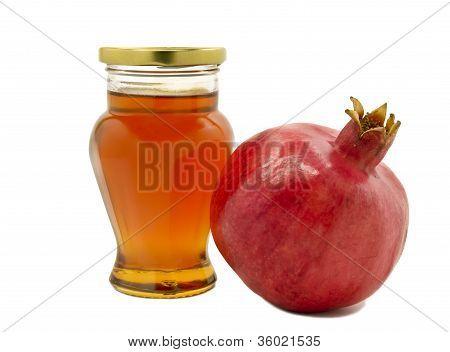 pomegranate and jar of honey isolated on white background
