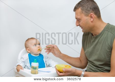 Man Feeding Baby With A Spoon