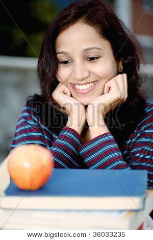 Young Teenage Girl Looking At Apple