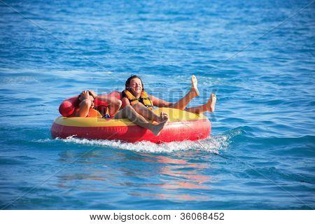 Friends Tubing On Sea