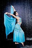 image of dancing rain  - girl executes east dance in the rain against a dark background - JPG