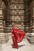 picture of khajuraho  - A woman with her red sari blowing in the wind - JPG