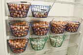 stock photo of chicken-wire  - A collections of wire baskets full of fresh organic eggs from a green farm - JPG