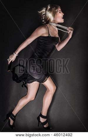 Beautiful angry woman running, wearing sexy black dress and luxury pearl beads, blond fashion model full body length, heartbroken female with mad facial expression, glamorous lady very upset