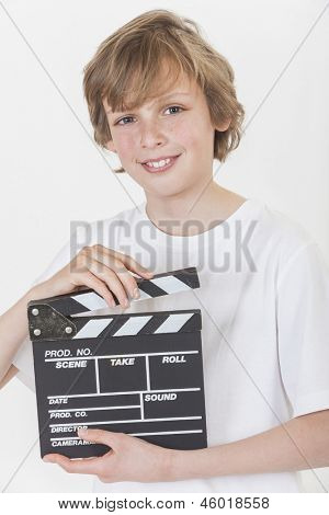 White background studio photograph of young happy boy smiling hand holding a filmmaker's clapperboard