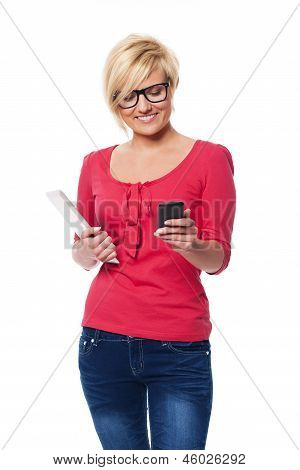 Fashion female using mobile phone and holding digital tablet