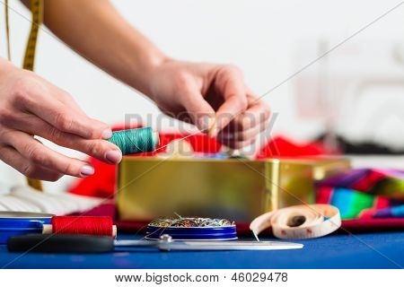 Freelance - tailor or designer working with different utensils, like cotton reels, spools, and colorful fabrics