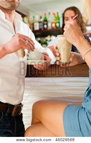 Attractive couple in cafe or coffeeshop, in the background the barista to be seen