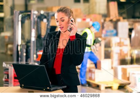Friendly Woman, dispatcher or supervisor using cell phone and laptop at warehouse of forwarding company, smiling, a forklift is in Background