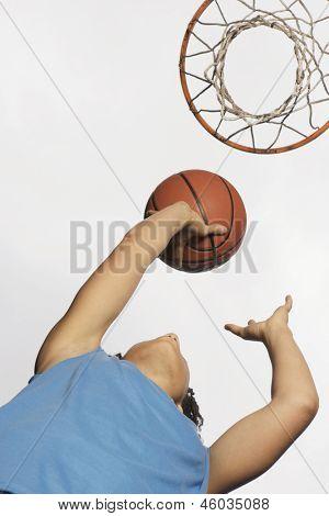 Low angle view of teenage girl shooting hoops