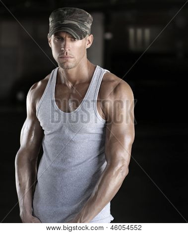 Muscular young sexy soldier man in camo army cap