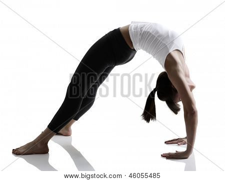 portrait of sport girl doing yoga stretching yoga exercise, studio shot in silhouette technique over white