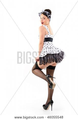Pinup girl on high heels in spotted dress stocking, full length portrait of seductive young happy sexy woman in pin-up style, over white