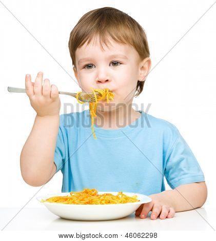 Little boy is eating spaghetti using fork, isolated over white