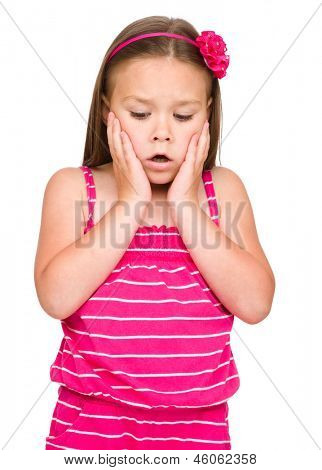 Little girl is holding her face in astonishment, isolated over white