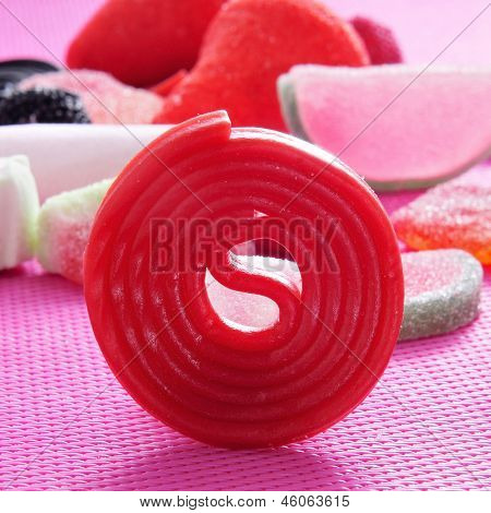 closeup of a red liquorice wheel and a pile of different candies