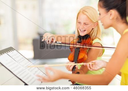 beautiful preteen girl in music class with music teacher