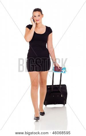 portrait of a businesswoman with a suitcase making a phone call against a white background