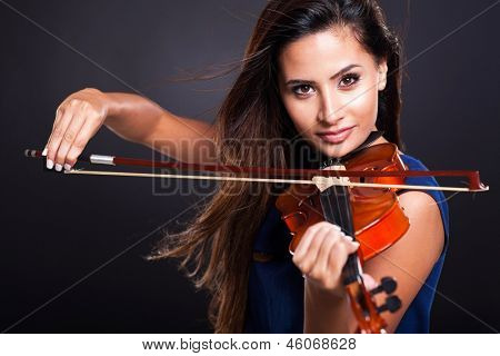 attractive young woman playing violin on black background