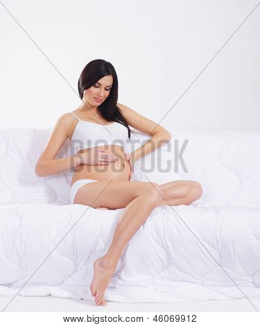 Young attractive pregnant woman with the beautiful belly over white background
