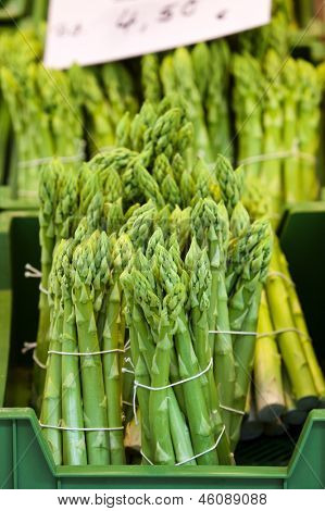 crate of bundled asparagus at farmer's market stand