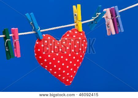 Red Heart Hanging On A Clothesline With Clothespins, Blue Background