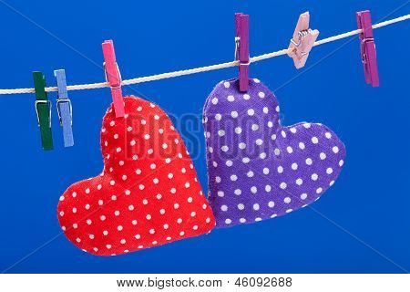 Two Hearts Hanging On A Clothesline With Clothespins, Blue Background