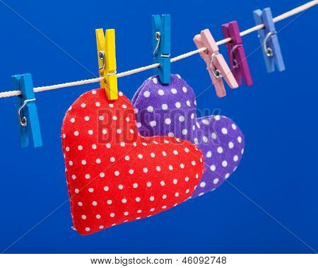 Two Hearts Hanging On A Clothesline With Clothespins, Focus On Red. Blue Background