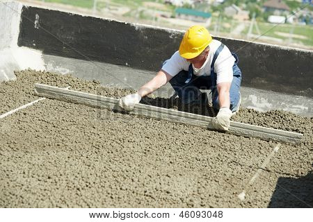 manual worker with float lute at roof construction works in building area