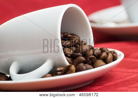 coffee beans in cup on red tablecloth